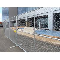 Temporary chain link fence with flat fence feet installed to secure the building construction site.
