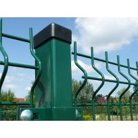 Curvy wire mesh fences are connected with a square post by green clips.
