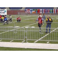 Several steel barricades are surrounding the sport field and many players in it.