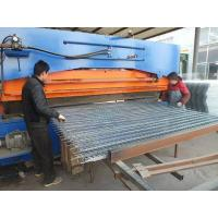 A bending machine is bending the welded wire mesh panels and two worker are working beside it.