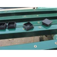 There are four black caps of square post are on the green square post.