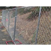 Temporary chain link fence with red square tubular fence feet installed by the roadside.