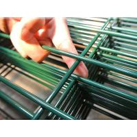A hand is holding the welding spot of welded wire mesh fence.