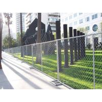 Temporary chain link fence with square tubular fence feet installed by the roadside.